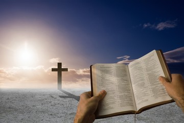 Composite image of man holding a holy bible