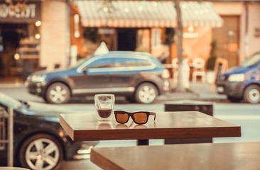 Drink on a table in a street cafe vith moving cars and bright store showcases