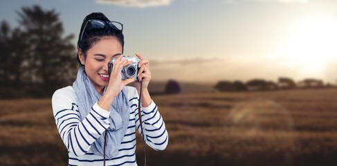 Composite image of smiling asian woman taking photograph with