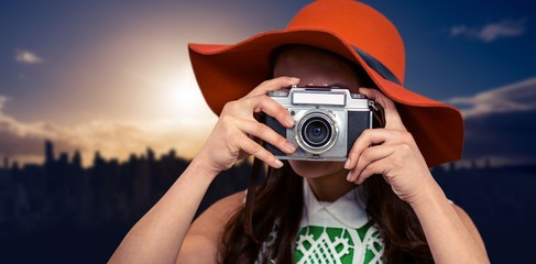 Composite image of woman with hat taking photograph with camera