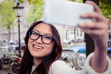 Composite image of smiling asian woman taking selfie