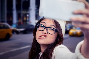 Composite image of asian woman making faces and taking selfie