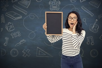 Composite image of surprised asian woman holding blackboard