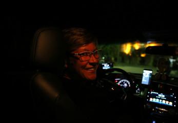 Paula Kaminski, a taxi driver from FemiTaxi app smiles for a photo inside his car in Rio de Janeiro