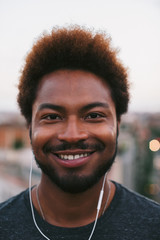 Portrait of a young african american man listening to music on a rooftop at sunset.