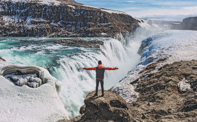 Hikier standing in front of Gullfoss waterfall in Iceland