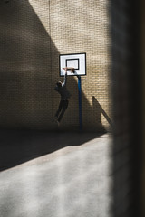 Young man hanging by a basket in urban area