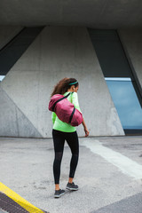 Young woman holding a sportbag walking on an urban outdoors.