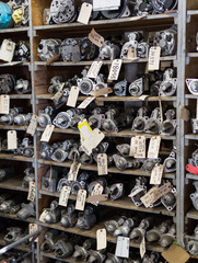 Carburetor parts shelf organized in vehicle mechanic shop with labels