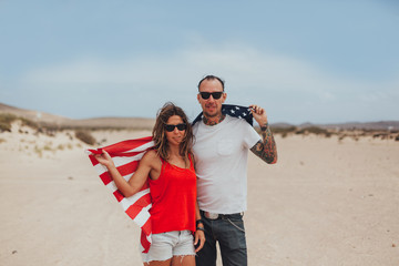 Latin Couple With a USA Flag in the Middle of the Desert