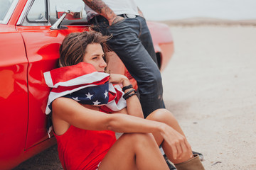 Couple Sitting Out of a Vintage Red Car in the Desert