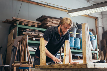 Carpentry - Young Bearded Man Applying Oil to Wooden Table in Industrial Workshop