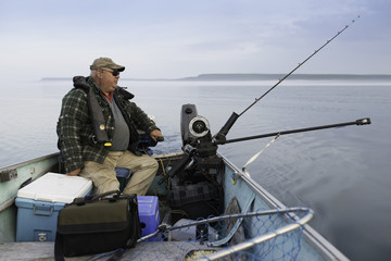 Overweight Middleage Man Fishing for Salmon In Boat With Downrigger on Georgian Bay
