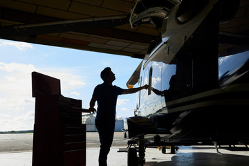 Silhouette Of Male Aero Engineer Working On Helicopter In Hangar