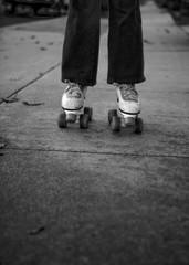 Child Wearing Old Fashioned Roller Skates On Sidewalk