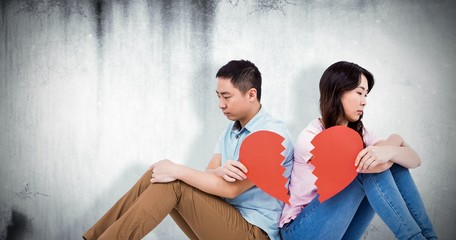 Composite image of sad couple holding broken heart pieces