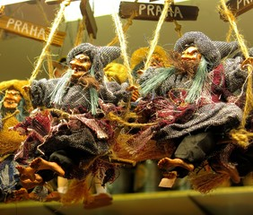 toy witch dolls on broomsticks at market in Prague, Czech republic