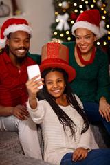 afro American family in Santa hats taking selfie on Christmas.