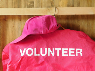 A pink jacket with a word volunteer on it is hanging on a hanger