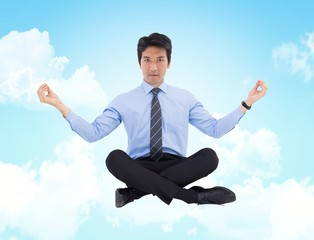Composite image of asian businessman doing yoga