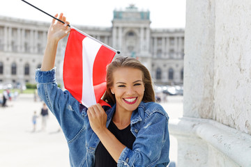 Happy young woman holding austrian flag in Vienna