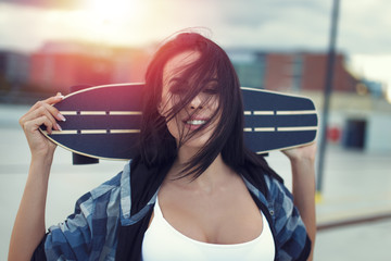 Young woman holding skateboard in sunset portrait