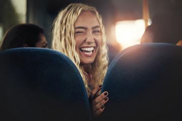 Young woman laughing and winking while sitting on a bus Wall mural