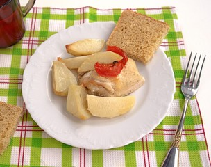 Delicious dinner of chicken baked in sour-cream sauce with potatoes and tomatoes