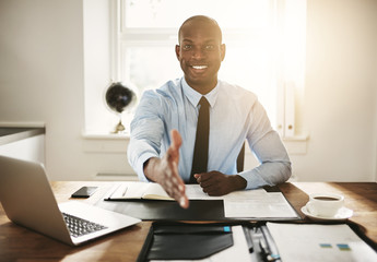 Smiling young executive sitting at his desk extending a handshak