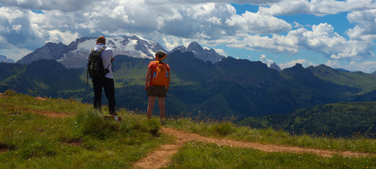 Two tourists with a Marmolada peak on the background, Dolomites, Italy