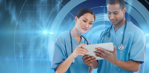 Composite image of surgeons looking at digital tablet in