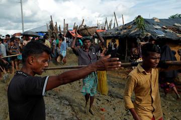 A Rohingya refugee man walks with a basket at Kutupalong refugee camp near Cox's Bazar