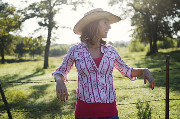 Western woman in cowboy hat wearing pink looks happy on rural farm.