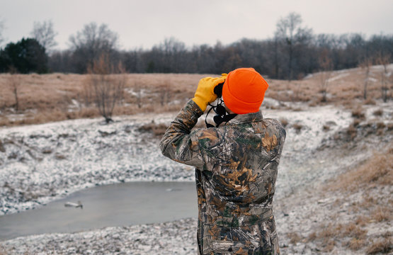 Man using binoculars to see scenic winter country landscape, dressed in camouflage.