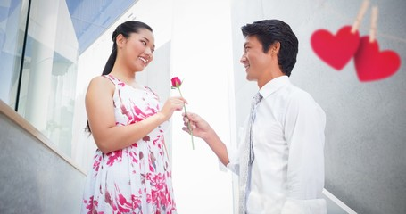 Composite image of man offering a red rose to girlfriend