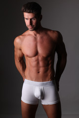 Young well build man is posing in white underpants.