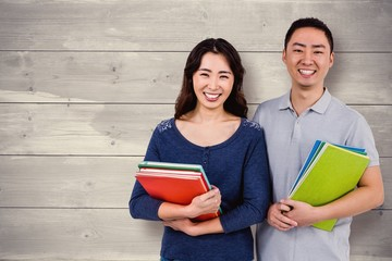 Composite image of happy couple holding books