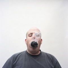 Overweight man with mouth full of lit cigarettes
