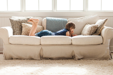 Girl lounging on couch reading a book