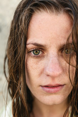Closeup of a young woman with wet hair looking at camera outdoors.