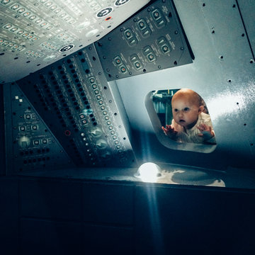 A baby looking through the window of an Apollo Space craft replica.