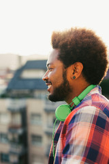 Side view of a young african american man with headphones standing on a terrace.