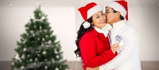 Composite image of festive senior couple exchanging gifts