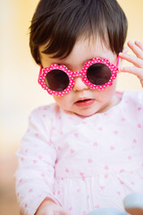 Stylish baby girl portrait wearing pink sunglasses
