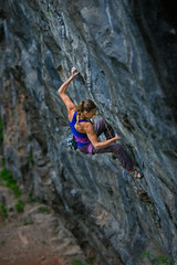 Fit young woman rock climbing a steep wall