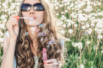 Young woman in meadow blowing soap bubbles