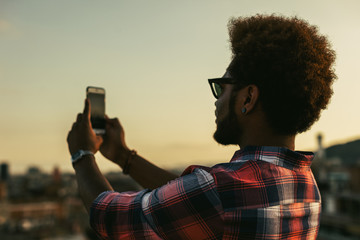 Young african american man taking a photo on his smartphone from a rooftop at sunset.