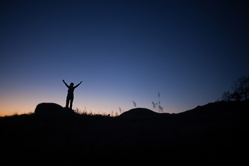 Woman in the landscape, silhouette at sunset