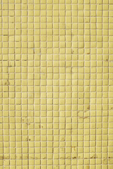 Yellow tile on wall, closeup