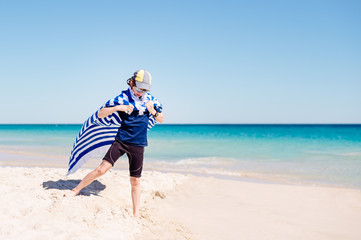 Boy tying a large striped blue and white towel as a cape at the beach in summer
